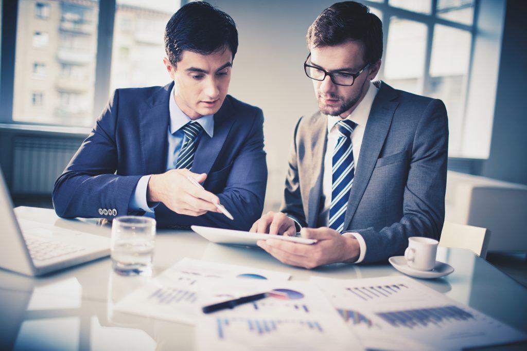 Men in ties looking at charts SS 174760658