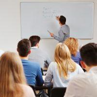 Teacher or man writing maths in front of class SS 133805693