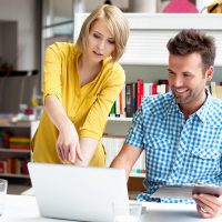 Man-and-woman-looking-at-laptop-SS-144275518